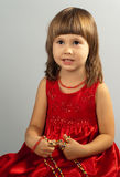 Bambina sveglia in un vestito rosso con la collana nella h Immagini Stock
