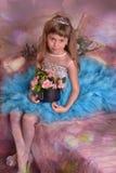 Bambina sveglia in una seduta blu del vestito immagine stock libera da diritti