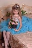 Bambina sveglia in una seduta blu del vestito fotografie stock