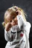 Bambina timida che sorride su un fondo nero fotografia stock