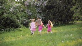 Bambina tre che tiene a mano che corrono sull'erba verde al giardino circondato dal ventilatore della bolla di aria stock footage