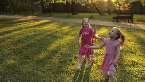 Bambina tre che tiene a mano che corrono sull'erba verde al giardino circondato dal ventilatore della bolla di aria archivi video
