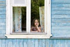 Bambina triste che guarda fuori la finestra della casa di campagna che pende il suo fronte sulla sua mano Fotografia Stock