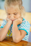 Bambina triste che si siede alla tabella Fotografie Stock