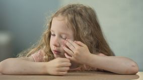Bambina triste che si siede alla tavola e che grida, l'abuso dei bambini, solitudine archivi video