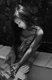bambina triste che si siede nelle ombre immagine stock