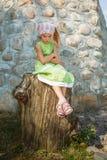 Bambina triste che si siede sul grande ceppo Fotografie Stock