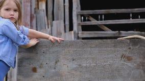 Bambina triste in vestiti blu accatastati su una barriera di legno stock footage