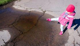 Bambina in un cappotto rosa, in jeans ed in stivali camminante il parco fotografie stock