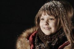 Bambina in un cappotto rosso che esamina la neve di caduta snowfall Immagini Stock Libere da Diritti