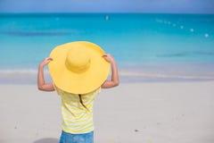 Bambina in un grande cappello di paglia giallo su bianco Fotografia Stock