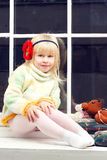 Bambina in un maglione e negli sguardi del knit la macchina fotografica fotografia stock libera da diritti