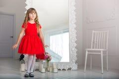 Bambina in un'occhiata malinconica del vestito rosso allo specchio fotografia stock