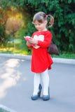 Bambina in un parco con un telefono dei bambini Fotografie Stock