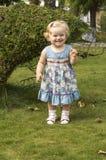 Bambina in un vestito lilla con capelli biondi Fotografie Stock