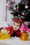 Bambina in un vestito rosso su fondo dell'albero di Natale immagini stock