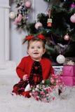 Bambina in un vestito rosso su fondo dell'albero di Natale fotografia stock libera da diritti