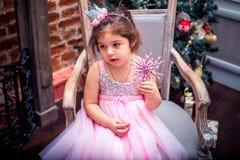 Bambina in un vestito vicino all'albero di Natale Fotografia Stock