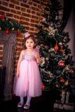 Bambina in un vestito vicino all'albero di Natale Fotografie Stock