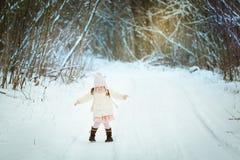 Bambina in una pelliccia bianca nella foresta di inverno immagine stock