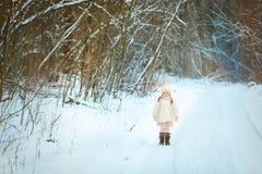 Bambina in una pelliccia bianca nella foresta di inverno fotografia stock libera da diritti