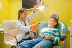 Bambina in uniforme che gioca dentista, stanza dei giochi fotografia stock