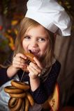 Bambina in vestiti del cuoco con i bagel nelle nel suoi mani e sorridere immagine stock