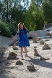 Bambina in vestito blu che gioca in caditoia al parco dalle pietre immagini stock