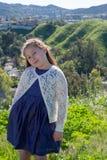 Bambina in vestito blu che sorride davanti al campo con i fiori e le colline nel fondo immagini stock