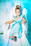 Bambina in vestito da principessa su un fondo di un fatato di inverno Fotografie Stock Libere da Diritti