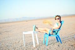 Bambina in vestito di bagno con il ventilatore in deserto caldo Immagine Stock