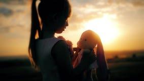 Bambina in vestito festivo rosa che tiene il grande giocattolo del coniglietto della peluche al tramonto Siluetta di un bambino c stock footage