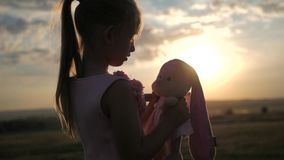 Bambina in vestito festivo rosa che tiene il grande giocattolo del coniglietto della peluche al tramonto Siluetta di un bambino c video d archivio