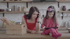 Bambina in vestito rosa che gioca sulla compressa che si siede sulla tavola La madre mette il canestro di vimini con pane sulla t stock footage