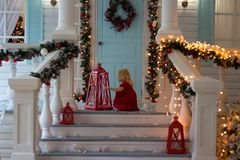 Bambina in vestito rosso che si siede sulla veranda della casa decorata, luci di Natale, ` s EVE del nuovo anno dopo saranno le l fotografia stock libera da diritti