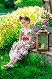 Bambina in vestito variopinto e fiori Immagine Stock