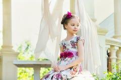 Bambina in vestito variopinto e fiori Immagini Stock