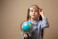 Bambina in vetri che tengono globo Fotografie Stock Libere da Diritti