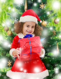 Bambina vicino all'albero di Natale con un regalo in sue mani Immagine Stock Libera da Diritti