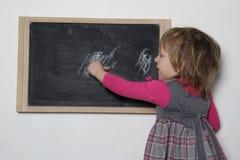 Bambina vicino alla lavagna Fotografia Stock
