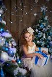 Bambina vicino a due alberi di Natale artificiali immagine stock libera da diritti
