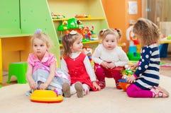 Bambine che giocano con i giocattoli in stanza dei giochi Immagine Stock