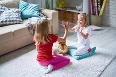 Bambine che giocano Pat-un-dolce fotografia stock
