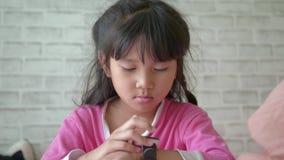 Bambine che per mezzo del suo dispositivo astuto dell'orologio video d archivio
