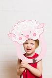 Bambine che tengono la maschera delle pecore su fondo bianco Fotografia Stock