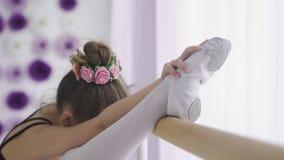 Bambine che utilizzano la sbarra di balletto quando fanno gamba che allunga gli esercizi nello studio di ballo archivi video