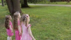 Bambine felici che giocano nel giardino e che giocano le bolle video d archivio