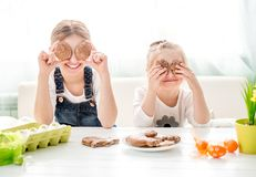 Bambine felici che tengono i biscotti di Pasqua davanti ai loro occhi Immagine Stock