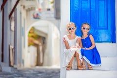 Bambine sveglie alla via del villaggio tradizionale greco tipico con le pareti bianche e le porte variopinte sull'isola di Mykono Immagine Stock