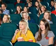 Bambine uscite che guardano film nel corridoio del cinema Immagine Stock